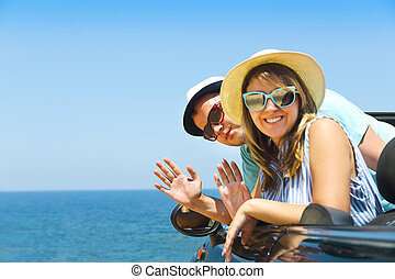 Portrait of a smiling couple at beach in the car