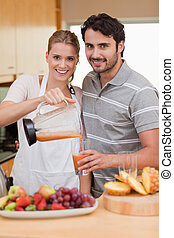 Portrait of a smiling couple drinking fruits juice