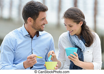 portrait of a smiling couple eating ice cream outdoors