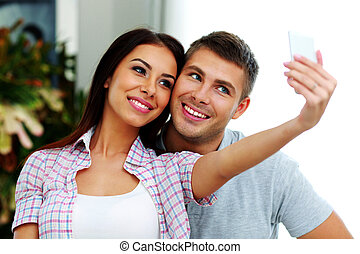 Portrait of a smiling couple making selfie photo with...