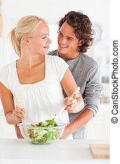 Portrait of a smiling couple preparing a salad