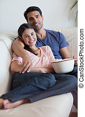 Portrait of a smiling couple watching television while eating popcorn in their living room
