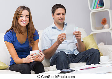 Portrait of a smiling couple with bills at home