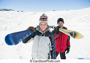 Portrait of a smiling couple with ski boards standing on snow covered landscape