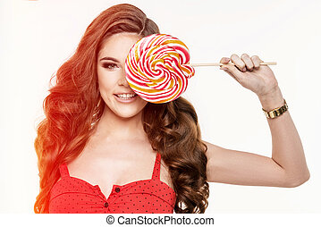 Portrait of a smiling cute girl covering her eye with lollipop