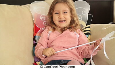 Portrait of a smiling cute little girl with angel wing