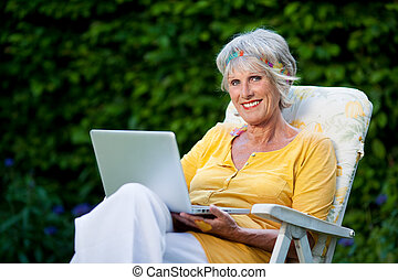 elderly lady using laptop in the garden - portrait of a...