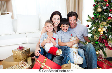 Portrait of a smiling family at Christmas time holding lots of presents at home