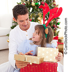 Portrait of a smiling father and his daughter opening Christmas presents in the living-room
