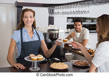 Portrait of a smiling female cafe owner with sweet snacks and couple at counter in the coffee shop