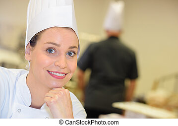 portrait of a smiling female cook in the kitchen