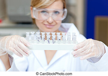 Portrait of a smiling female scientist holding different samples in her laboratory
