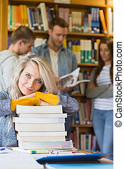 Portrait of a smiling female student with stack of books while others in background at the college library