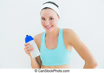 Portrait of a smiling fit woman holding water bottle