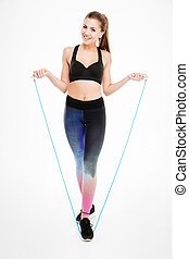Portrait of a smiling fitness woman jumping with skipping rope
