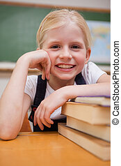 Portrait of a smiling girl leaning on books
