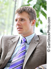 Portrait of a smiling handsome young businessman sitting on chair in office