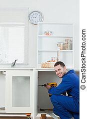 Portrait of a smiling handyman fixing a door