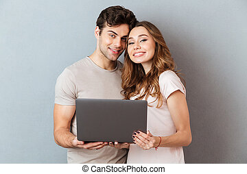Portrait of a smiling happy couple holding laptop computer