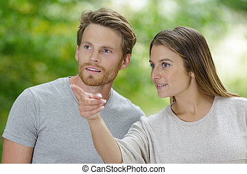 portrait of a smiling happy couple pointing finger away