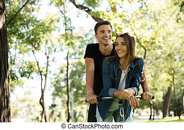 Portrait of a smiling happy couple riding on a bicycle