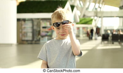 Portrait of a smiling little boy in an airport building wearing sunglasses.