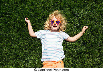 Portrait of a smiling little girl in heart shaped sunglasses lying on green grass