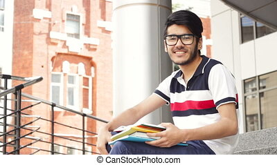 Portrait of a smiling male asian student sitting on stairs...