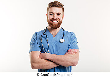 Portrait of a smiling male doctor standing with arms folded