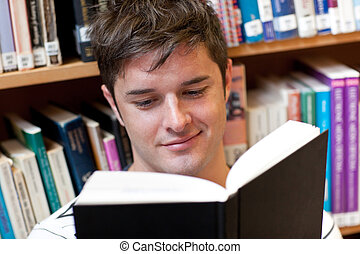 Portrait of a smiling male student reading a book sitting on the floor in a bookshop