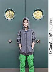 portrait of a smiling male teenager in front of a green metal door, with two portholes.
