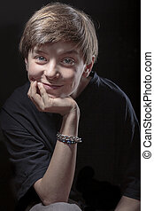 portrait of a smiling male teenager with black background