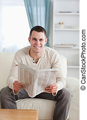 Portrait of a smiling man holding a newspaper