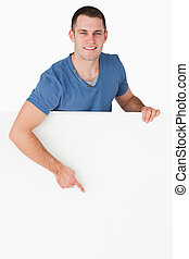 Portrait of a smiling man pointing at a blank panel