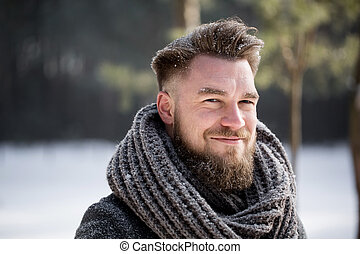 Portrait of a smiling man wearing winter coat in white forest