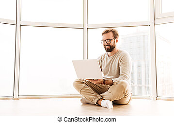 Portrait of a smiling man working on laptop computer