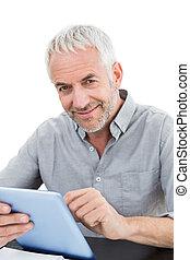 Portrait of a smiling mature businessman using digital...
