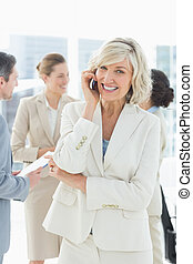 Portrait of a smiling mature businesswoman on call with colleagues discussing in background at a bright office