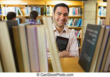 Portrait of a smiling mature student holding book by shelf with men in background at the library