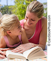 Portrait of a smiling mother and her daughter reading at a picnic in a park
