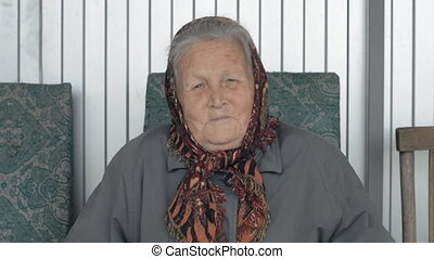 Portrait of a smiling old woman in a brown kerchief.