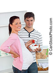 Portrait of a smiling pregnant woman eating strawberries and of her husband at home
