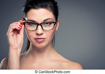 Portrait of a smiling pretty, young woman wearing glasses with copy space - studio shot, color toned