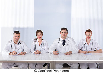 Smiling Professional Doctors At Desk