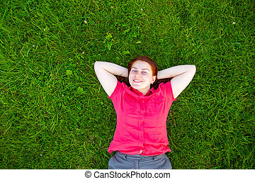 Portrait of a smiling red-haired young girl on green grass