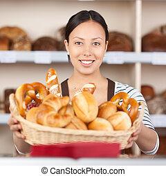 smiling saleswoman holding breadbasket in bakery - portrait ...