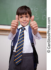 Portrait of a smiling schoolboy with the thumbs up