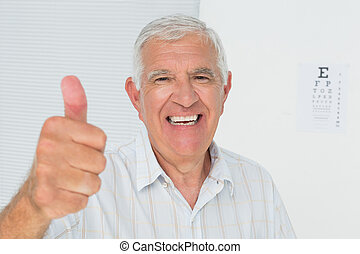 Portrait of a smiling senior man gesturing thumbs up with eye chart in the background at medical office