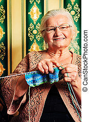 spokes - Portrait of a smiling senior woman knitting on...