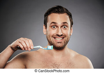 Portrait of a smiling shirtless man holding toothbrush